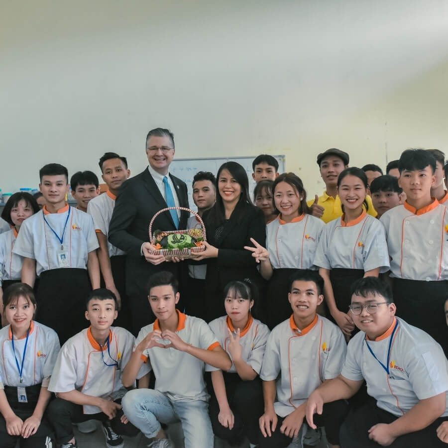 A GROUP PHOTO OF REACH COOKING STUDENTS AND THE U.S AMBASSADOR TO VIETNAM