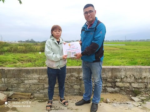 Ly, at the left, was receiving VND 1 million from REACH in flood recovery support